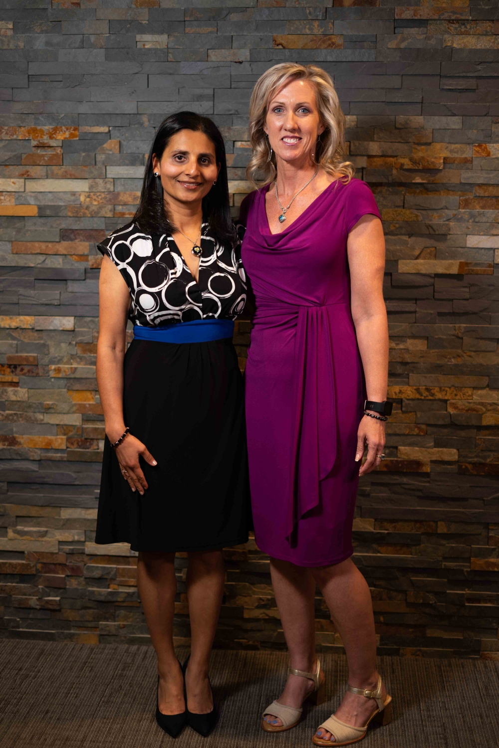 Rebecca McGowan & Payal Soni-Patel Physcians Assistants For Asheville Neurology Standing In Front of a Wall